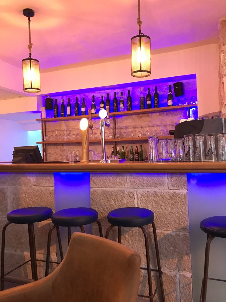 A hotel bar with stools, a counter and 2 lampshades
