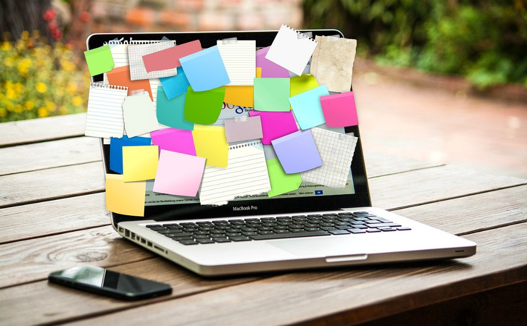 Laptop with post-it notes on the screen - — full time travel blogger