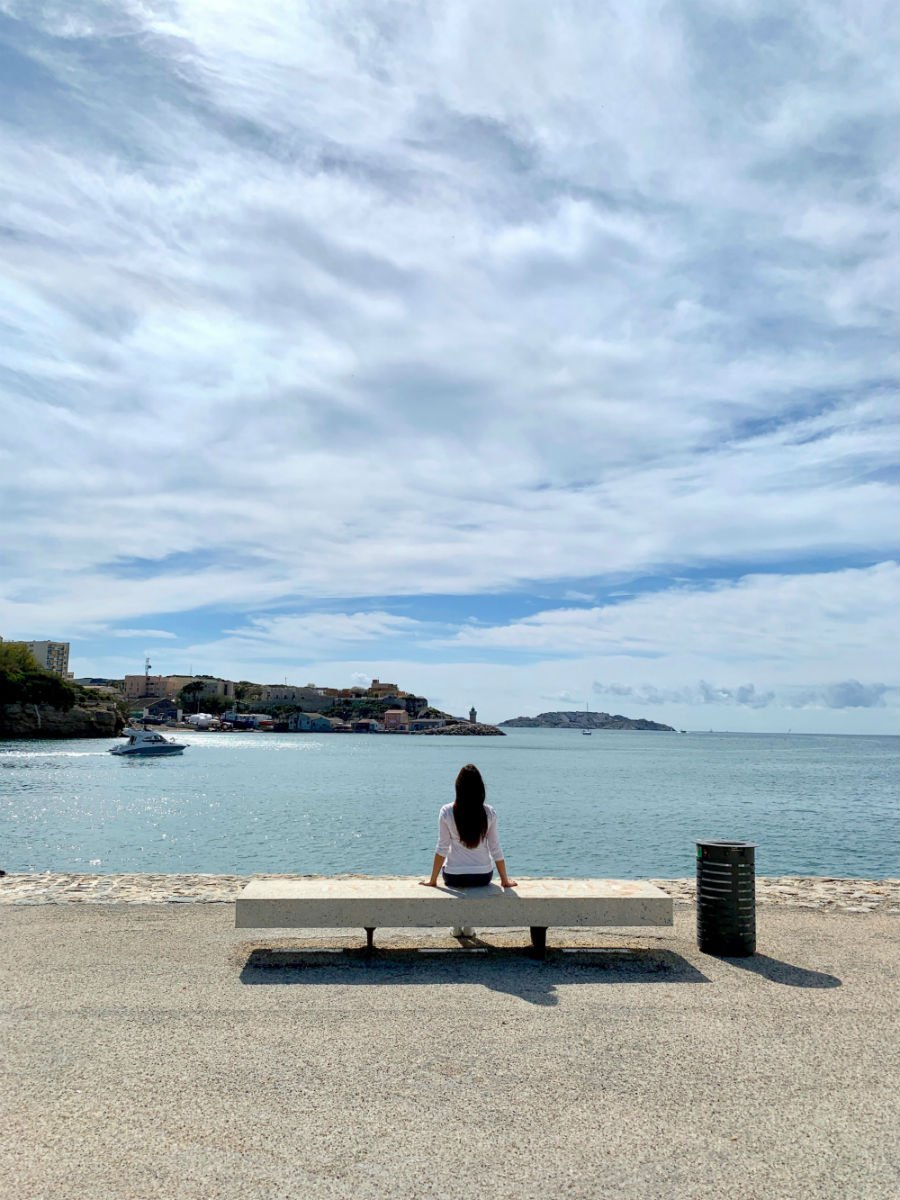 Lisa Rivera sitting on a bench overlooking the sea in Marseille — things to know about Marseille