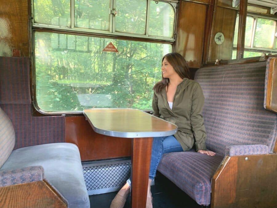 Lisa Rivera sitting on steam train - Lake District short breaks