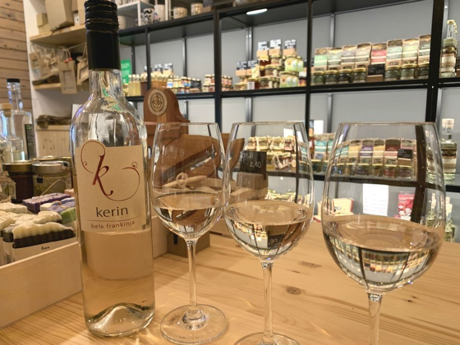 3 wine glasses on a table and a bottle of Kerin Bela Frankinja