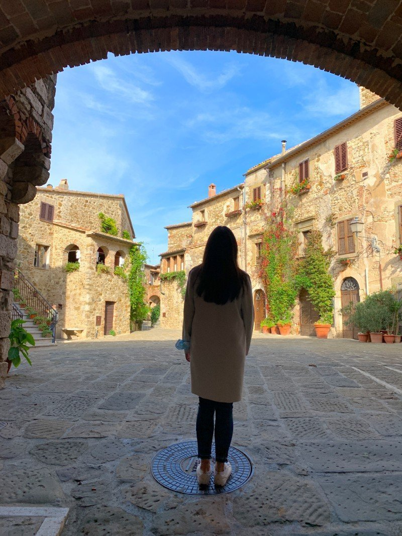Lisa Rivera standing before Piazza del Castello - a village in Tuscany